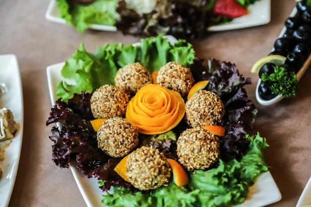 Palline di sesamo con lattuga, arancia e olive
