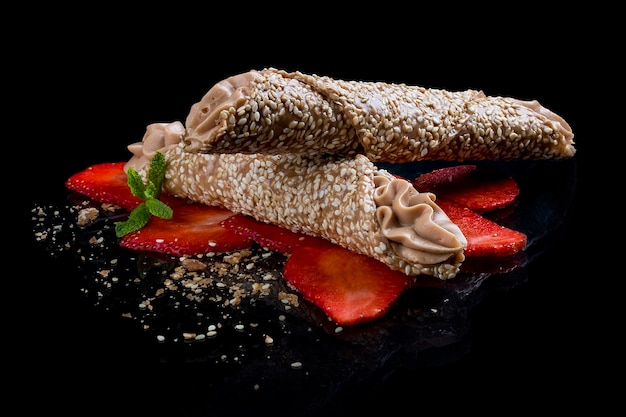 Sesame and caramel tube with mascarpone cream on a black background
