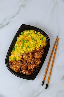 Sesame chicken teriyaki with rice and chopstick. food delivery.