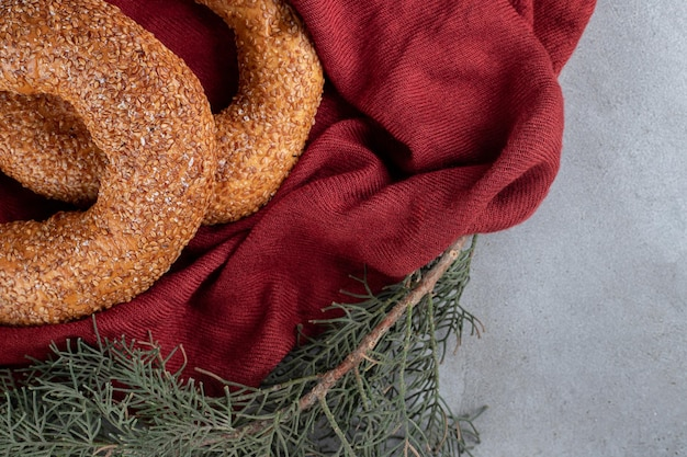 Sesame coated bagels sitting in a decorative arrangement on marble surface