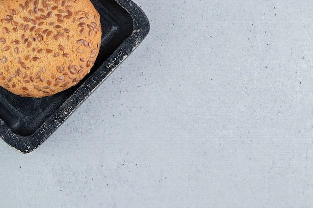 Biscotti ricoperti di sesamo su un vassoio nero su fondo di marmo.