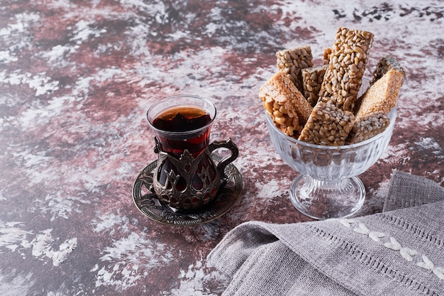 Sesame cookies in a cup with a glass of tea.