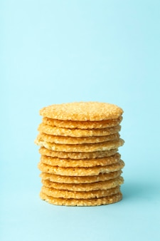 Кунжутное печенье на синем фоне. выпечка и сладости фон. концепция домашней кухни
