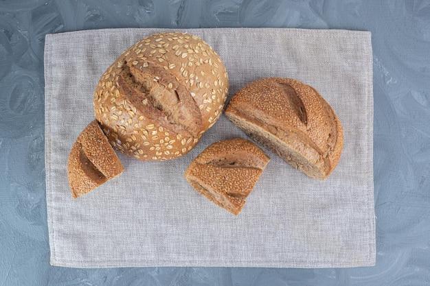Pezzi di pane a fette ricoperti di sesamo su un asciugamano sulla superficie di marmo.