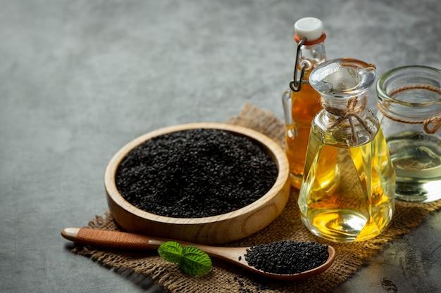 暗い背景にゴマ油と生の黒ごま