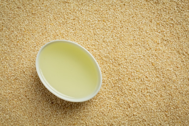 Кунжутное масло и семена кунжута на мраморном фоне