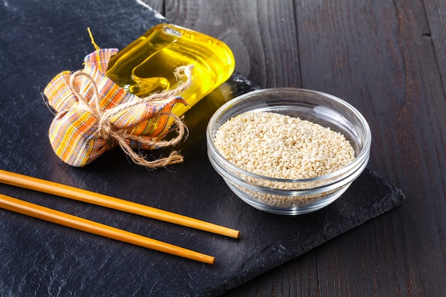 Sesame oil in a bottle and sesame seeds in the cup - a source of vitamin e, calcium, phosphorus
