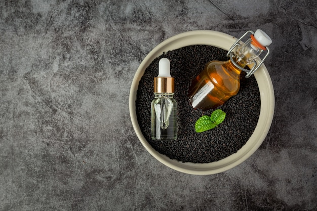Olio di sesamo e semi di sesamo nero crudo su sfondo scuro