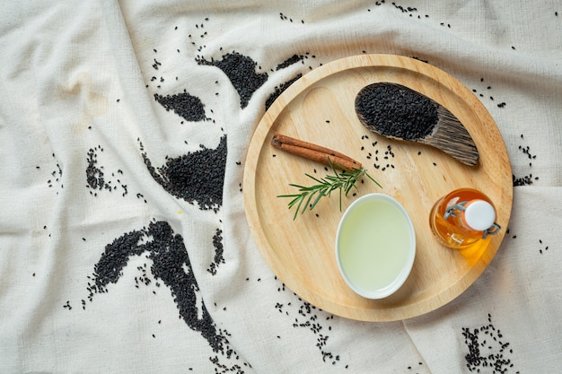 Sesame oil and raw black sesame seeds on marble background