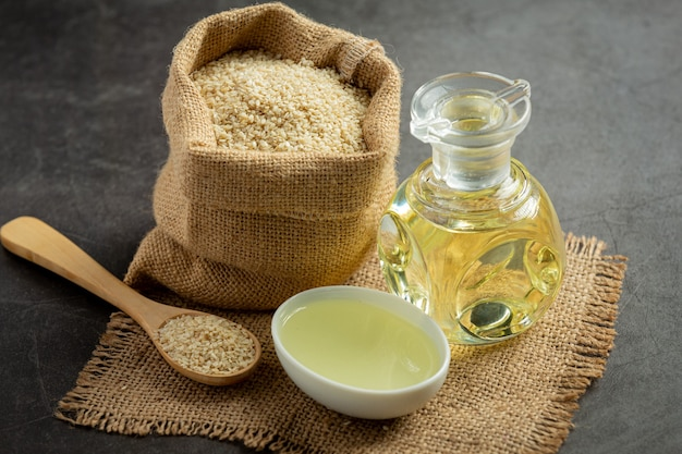 Sesame oil and sesame seeds on dark background