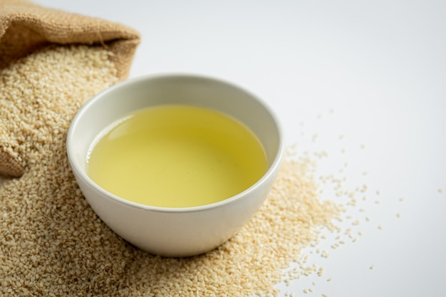 Sesame oil and sesame seeds on marble background