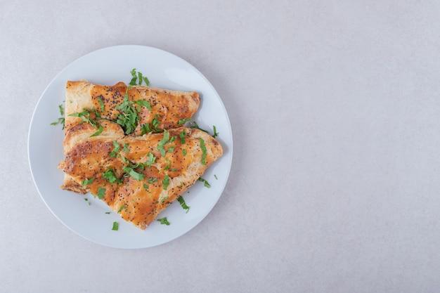 Pita di sesamo con prezzemolo tritato su piatto su tavola di marmo.