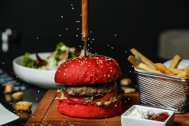 牛肉のハンバーガーにごまを注ぐ