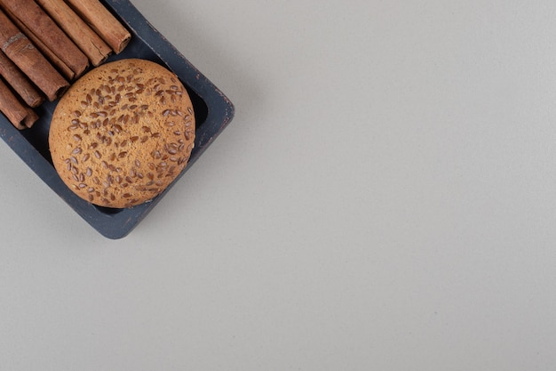 Sesame seed coated cookie and a bundle of cinnamon sticks on a small tray on marble background.