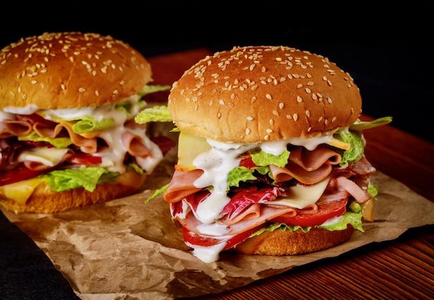 新鮮な野菜と木の板にハムとゴマのサンドイッチ