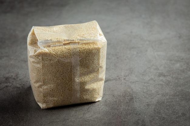 Sesame seeds in bag on dark background