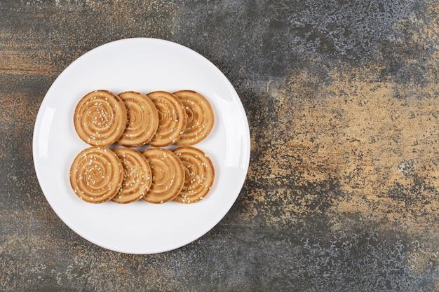Biscotti ai semi di sesamo sulla zolla bianca.