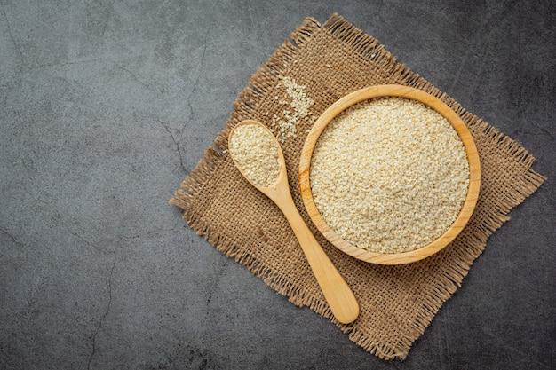 Sesame seeds in bowl on dark background