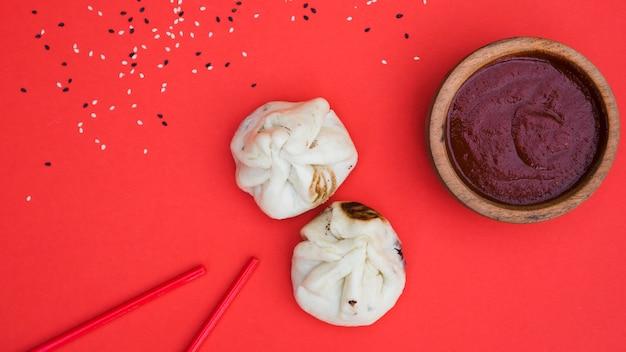 Семена кунжута; палочки для еды; пельмени и соусы в деревянной миске на красном фоне