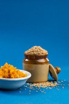 Семена кунжута в глиняном горшке с джаггери в миске на синем фоне