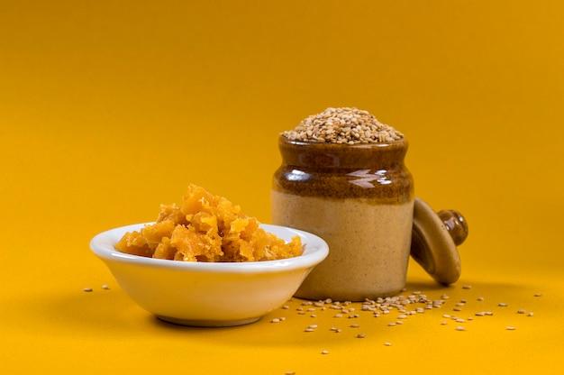 Семена кунжута в глиняном горшке с джаггери в миске на желтом фоне