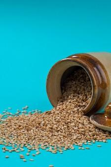Sesame seeds in pot on blue