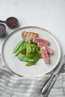 참깨 참치 스테이크 구이 봄 양파와 설탕 스냅 완두콩 세트, 접시에, 흰 돌에
