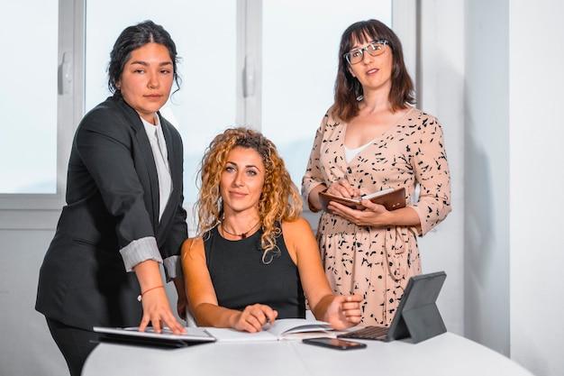 Сессия молодых предпринимателей в офисе, две молодые кавказские девушки и молодая латина в офисе готовят видеоконференцию
