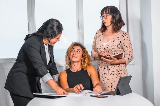 Сессия молодых предпринимателей в офисе, две молодые кавказские девушки и молодая латина в офисе разговаривают друг с другом
