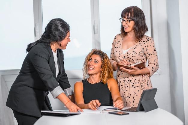 Сессия молодых предпринимателей в офисе, две молодые кавказские девушки и молодая латина в офисе беседуют