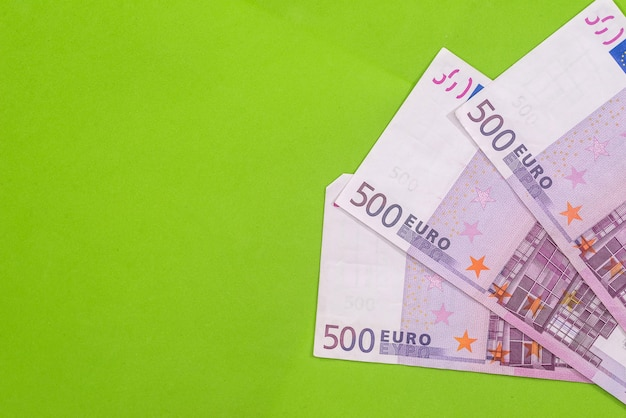 Set of 500 euro banknotes on green surface