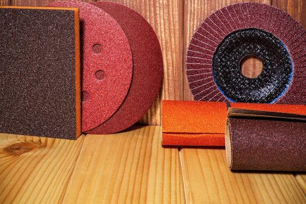 Set of abrasive tools and sandpaper on brown vintage wood background
