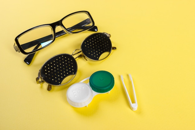 A set of accessories for sight. pinhole glasses, lenses with container and glasses for sight. pair of medical pinhole glasses with reflections.