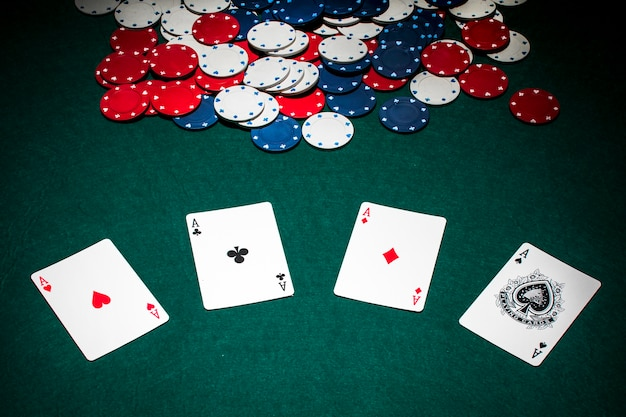 Set of aces playing card and casino chips on green poker table