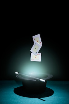 Set of aces playing cards in mid-air over the illuminated black top hat