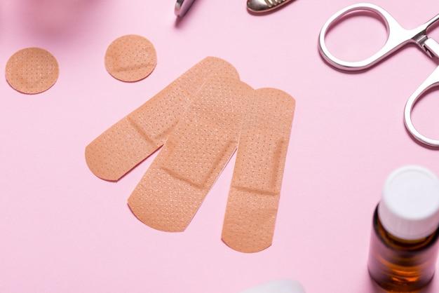 Set of adhesive bandage, medical sticking plaster on pink background
