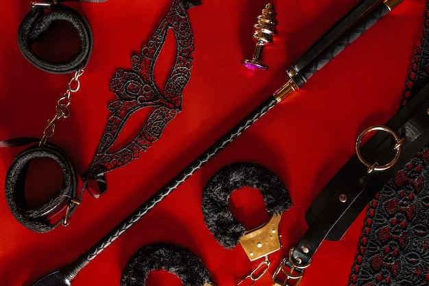 Set of adult toys on a red silk sheet, top view