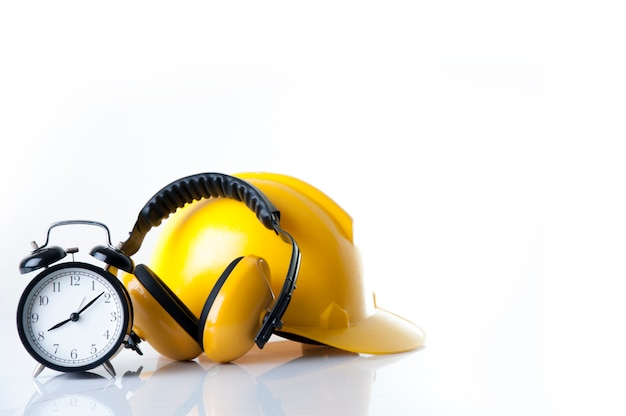Set alarm clock to wear safety ear muffs leather with helmet for worker