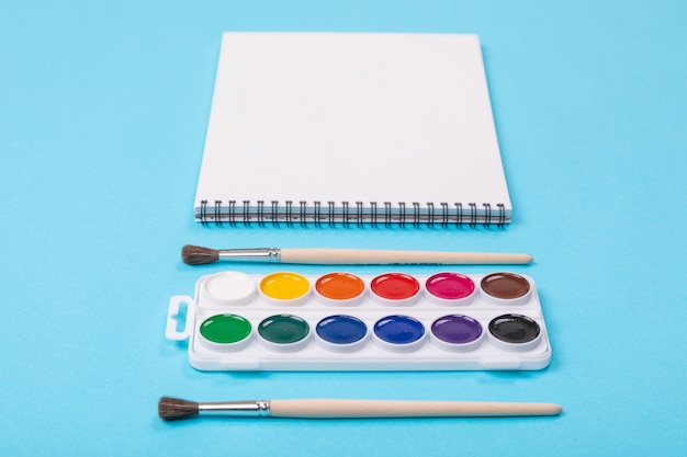 Set of aquarelle paints with brushes and album for painting isolated on blue background