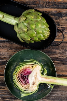 Set of and artichoke and slice in a pot and plate on a dark wooden background. top view.