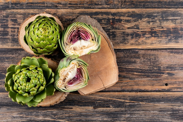 Set of artichokes and slices on small stubs and dark wooden background. top view.