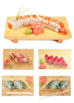 白い背景で隔離の木製プレートにアジア料理の寿司を設定します。