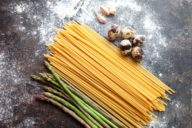 Set of asparagus, eggs and garlic and spaghetti on a dark textured background. top view.