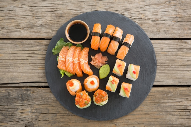 Set of assorted sushi served on black stone slate