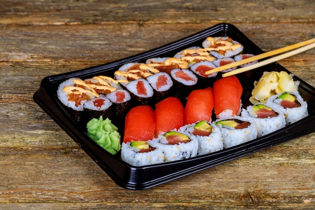 Set of assorted sushi served plastic box on wooden table