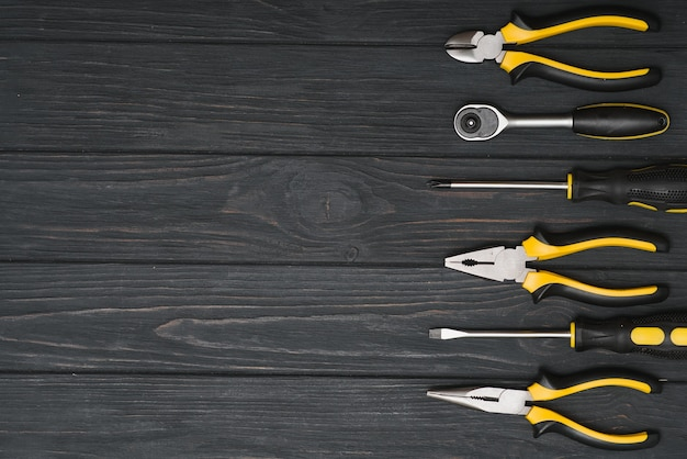 Set of assorted work carpentry and locksmith tools on a dark wooden background with copy space.