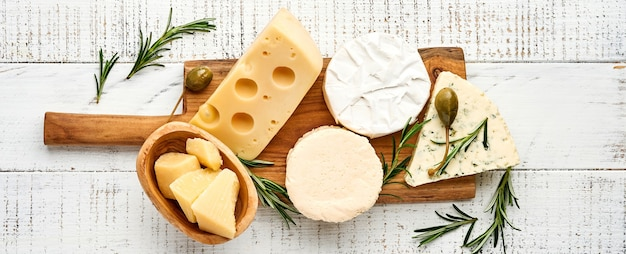 Set or assortment cheeses. suluguni with spice, camembert, blue cheese, parmesan, maasdam, brie cheese with rosemary and pepper. on white wooden old background. top view. copy space. banner.