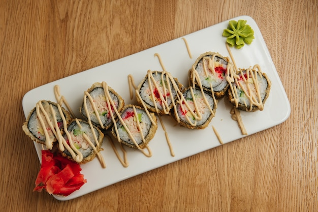 Set of baked sushi rolls with wasabi and ginger on white plate. japanese oriental cuisine