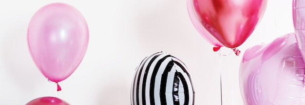 Set of balloons in the form of a heart and round pink and striped on light background with copy space. long wide banner.