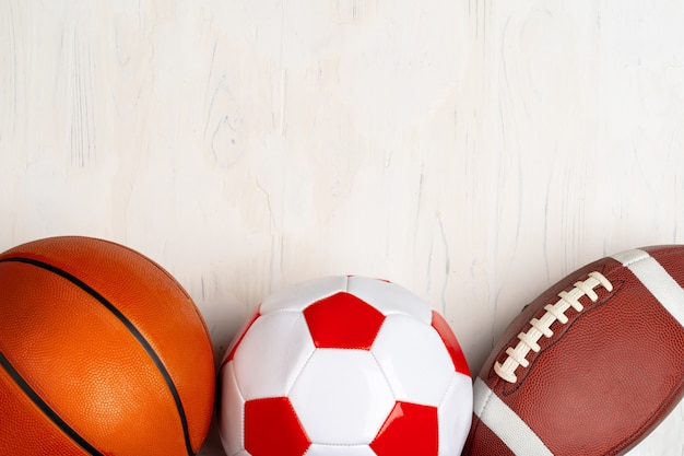 Set of balls for soccer, basketball and rugby on wooden background